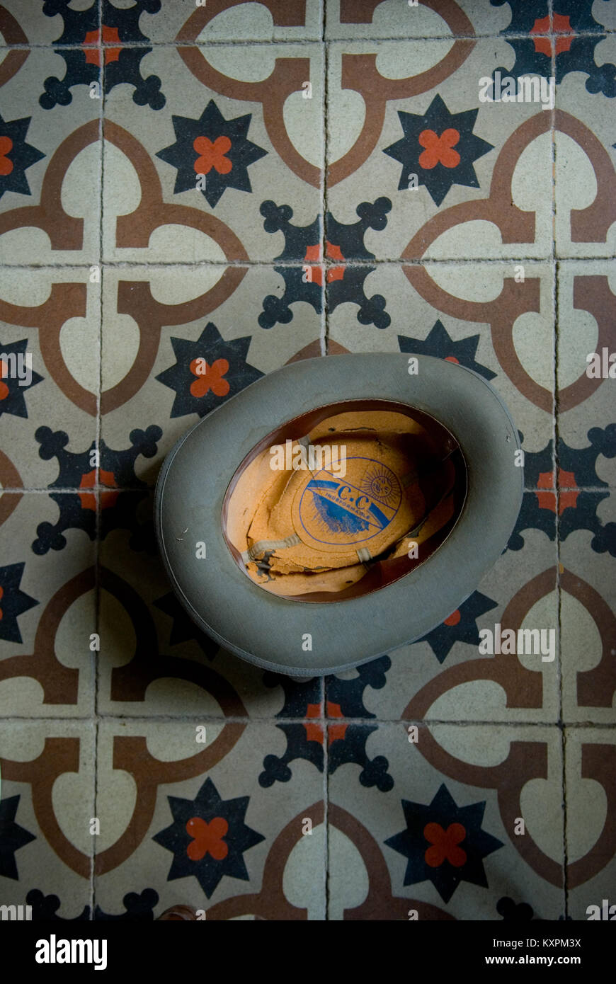 An Old Grey Trilby Hat Lies Upside Down On A Beautiful French Tiled