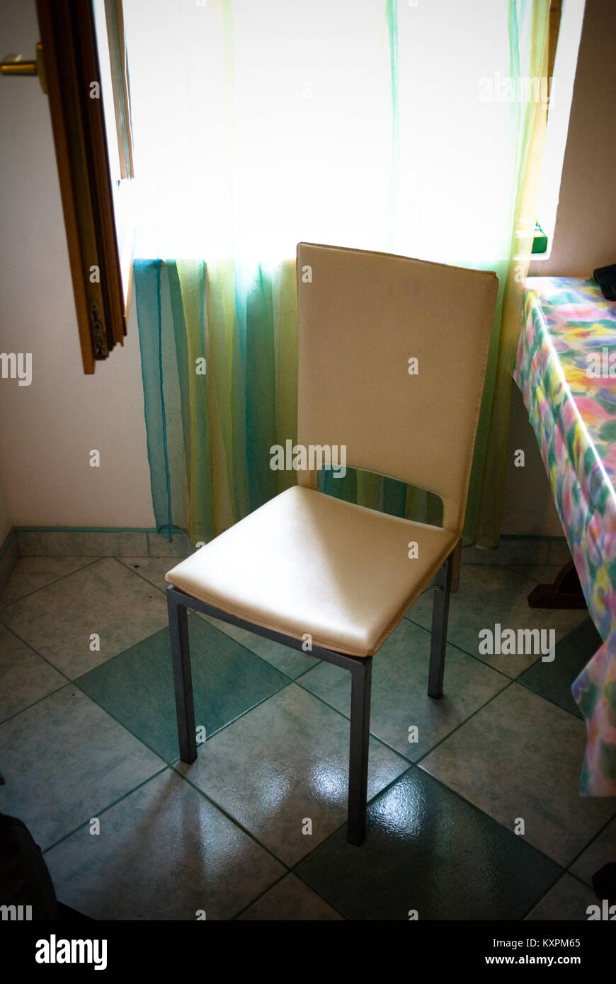 a single empty chair on a tiled kitchen floor near a curtained ...