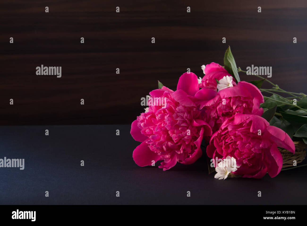 bouquet of pink peony and small white flowers on dark background ...