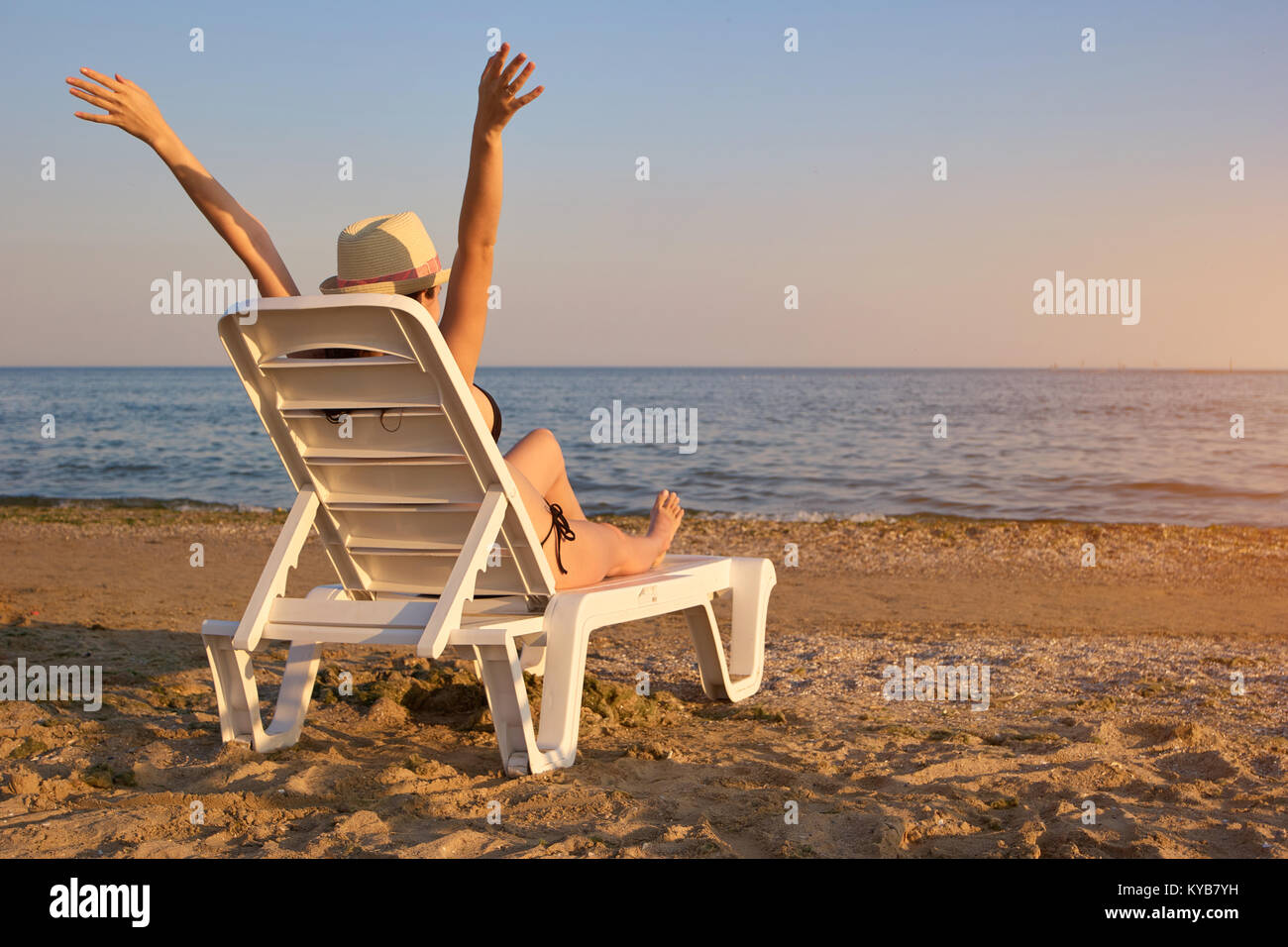 relaxing at the beach in the evening backside view stock photo