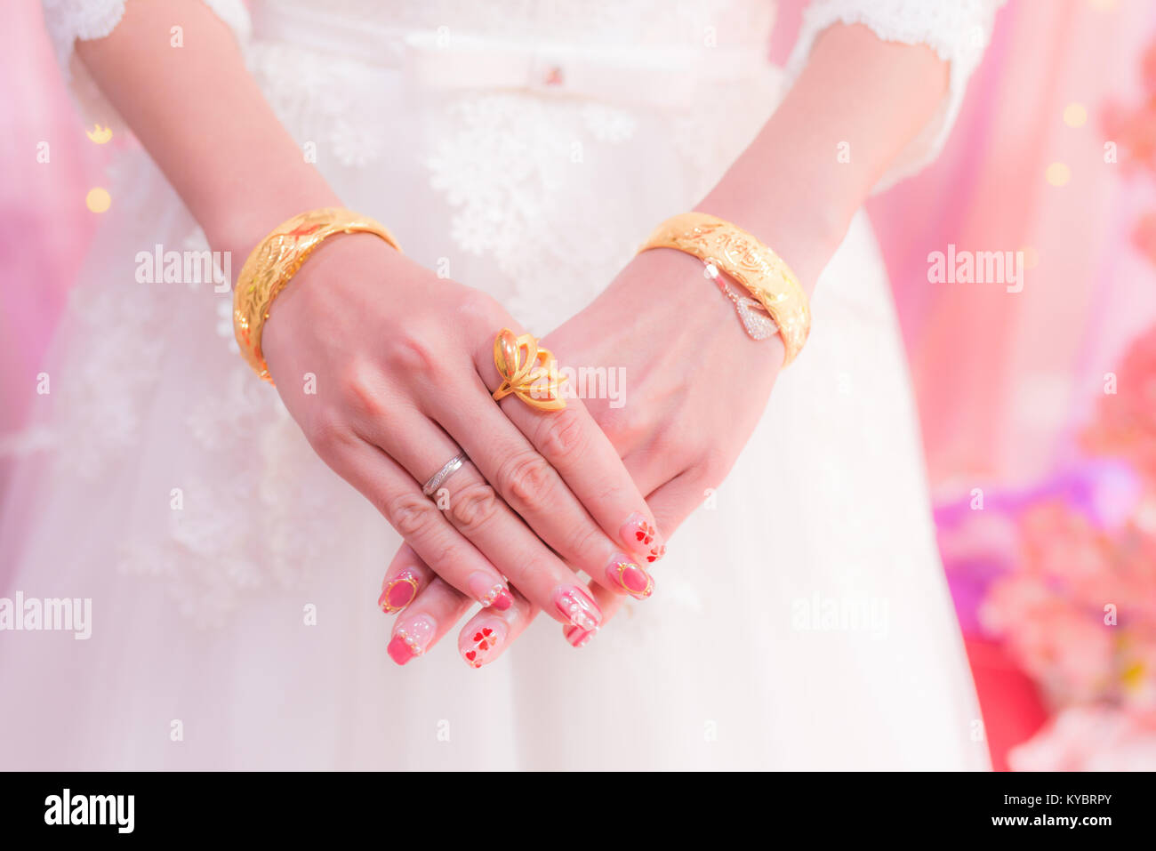 bride showing her hands with gold wedding ring and bracelets Stock ...