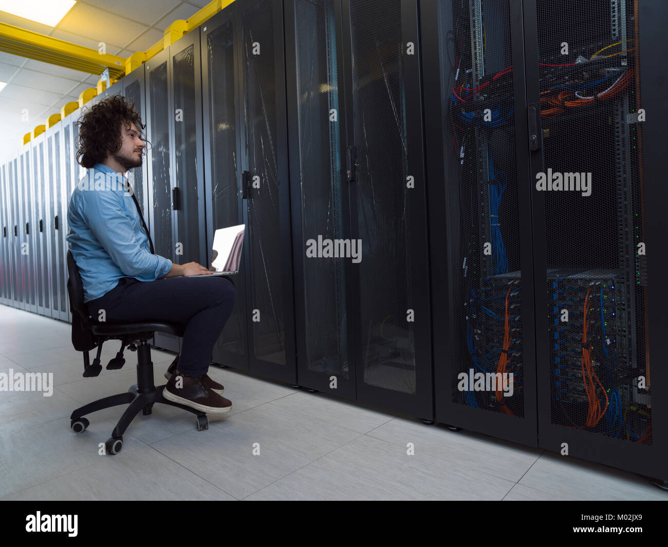 Male IT engineer working on a laptop in server room at