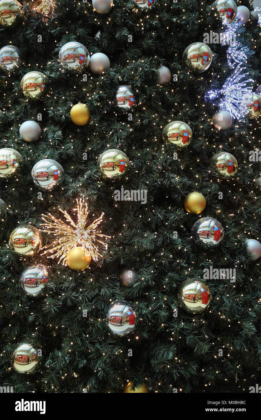 christmas tree decorated with christmas gold and silver ball hanging on tree with sparkling and twinkling lights in holiday and festive background