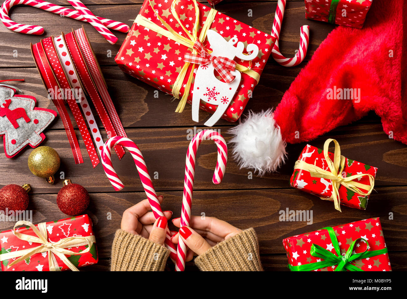 Woman holding Christmas decorations over an old wooden table. Close ...