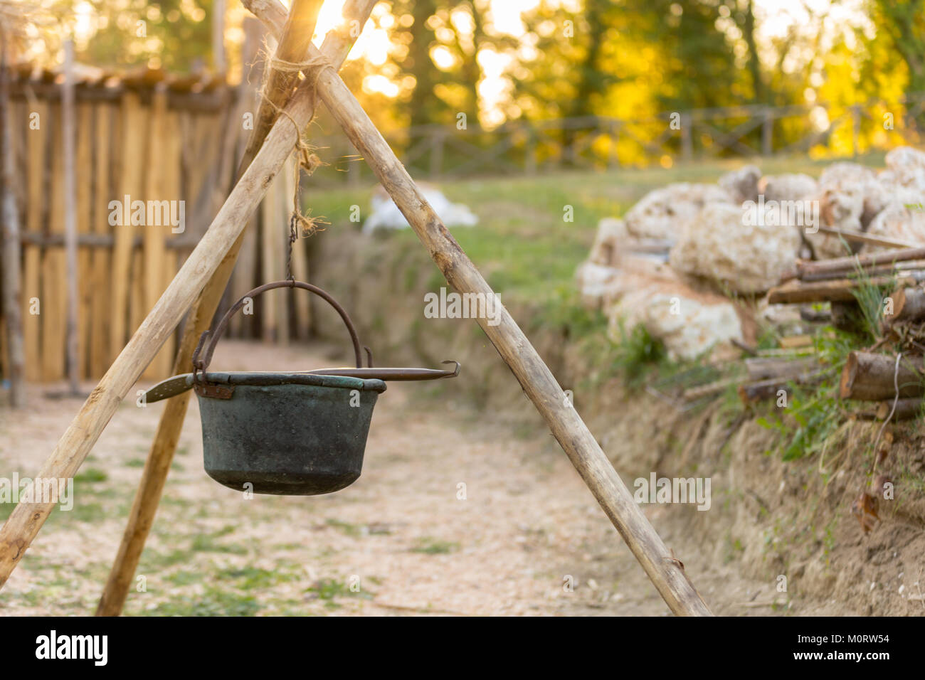 beautifull ancient copper pot tied to logs to cook food stock photo