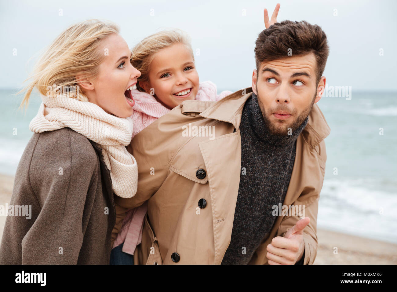 Portrait Of A Funny Family With Little Daughter Having Fun At The Beach Together