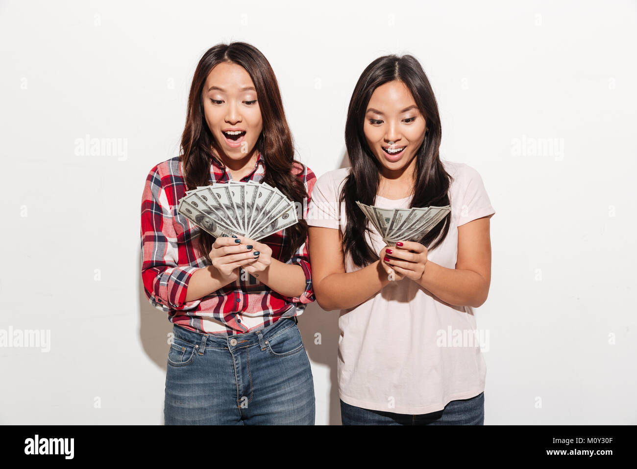 photo of two asian pretty shocked cute ladies sisters standing stock