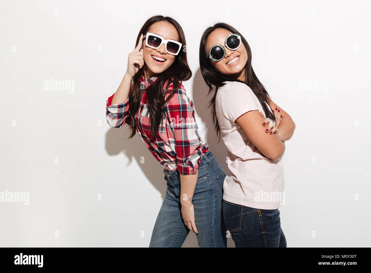 photo of two asian pretty cute ladies sisters wearing sunglasses