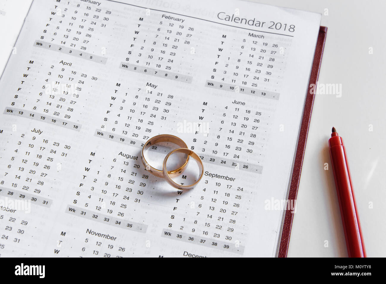 planning a wedding in 2018 calendar of 2018 two wedding rings and a pen on white background
