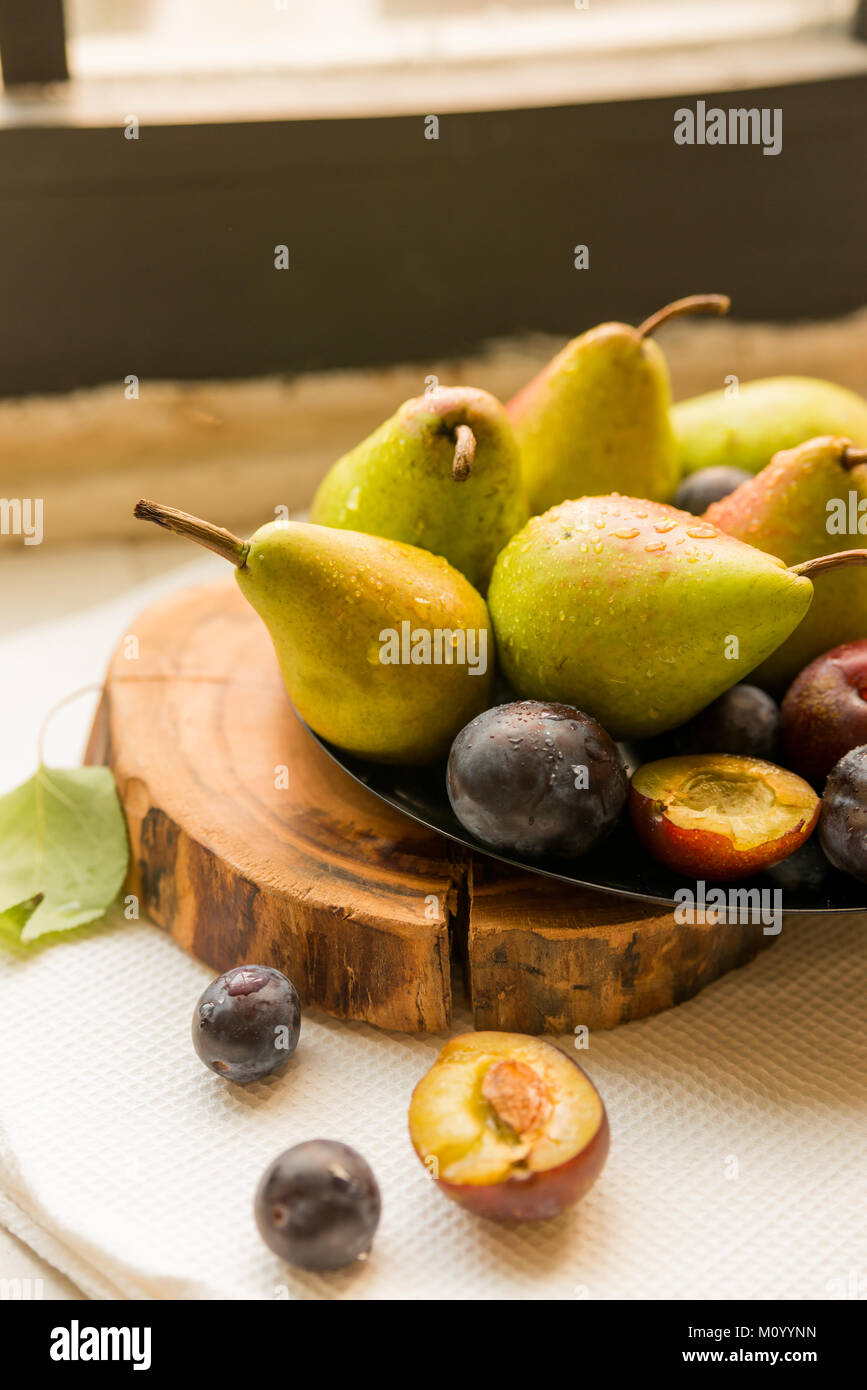 studio shot plums and pears on plate heathy diet stock photo