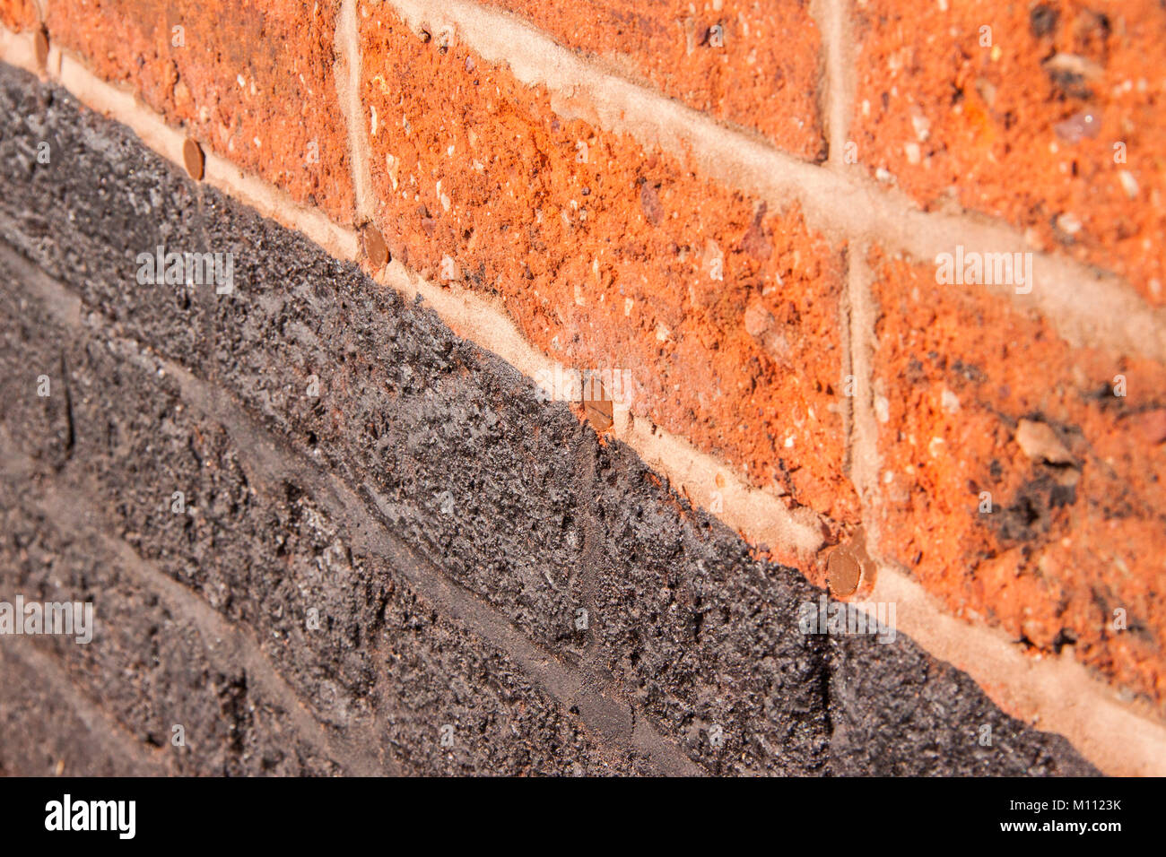 Red Brick Wall Showing Holes Filled Over After A Damp Proof Course Was Injected Into The Brickwork