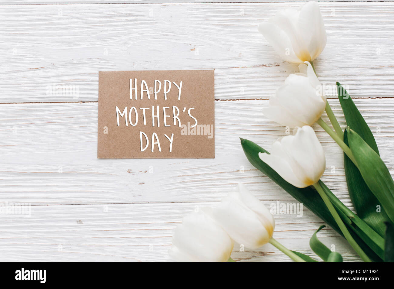 Happy mothers day text sign on stylish greeting card and tulips on happy mothers day text sign on stylish greeting card and tulips on white wooden rustic background flat lay with flowers and gift blank paper with spa kristyandbryce Choice Image