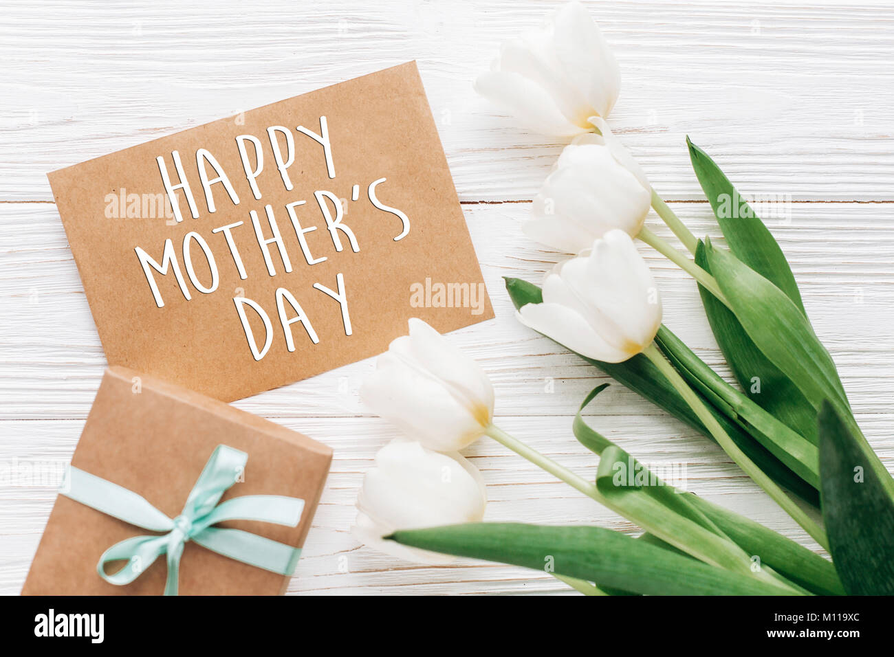 Happy mothers day text sign on stylish craft present with greeting happy mothers day text sign on stylish craft present with greeting card and tulips on white wooden rustic background flat lay with flowers and gift w kristyandbryce Choice Image