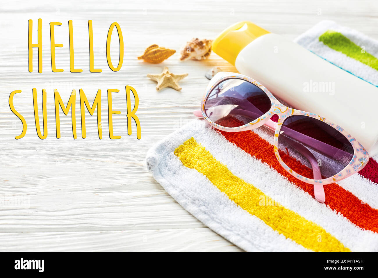 Hello Summer Text On Colorful Towel, Sunglasses, Yellow Sunscreen And Star  Shells On White Rustic Wooden Background, Top View. Space For Text. Travel