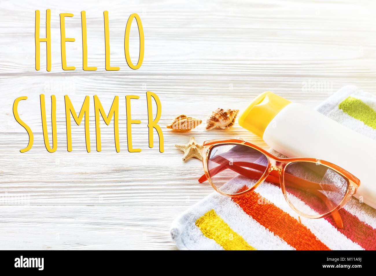 Hello Summer Text On Colorful Towel, Sunglasses, Yellow Sunscreen And Star  Shells On White Rustic Wooden Background, Top View. Space For Text. Sunny S