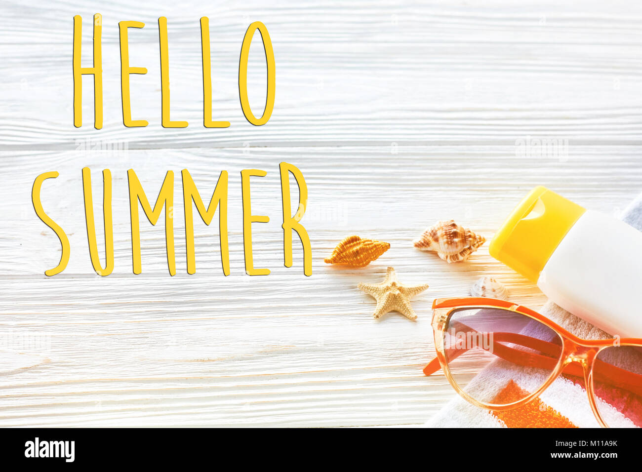 Hello Summer Text, Vacation Concept. Colorful Towel, Sunglasses, Yellow  Sunscreen And Star Shells On White Rustic Wooden Background, Top View.  Space F