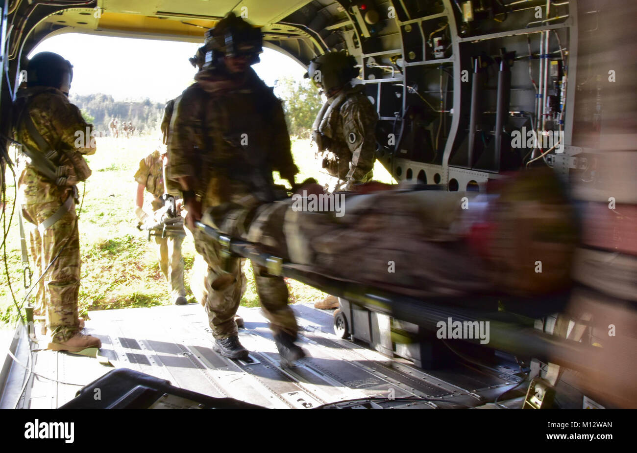 Parajumpers with 212th, Rescue Squadron, Alaska Air National Guard assist injured Soldiers on board the aircraft during pararescue training at Kahuku, ...