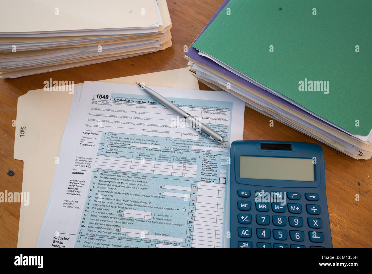 1040 tax form stock photos 1040 tax form stock images alamy irs tax form with tax records in folders calculator and pen stock image falaconquin