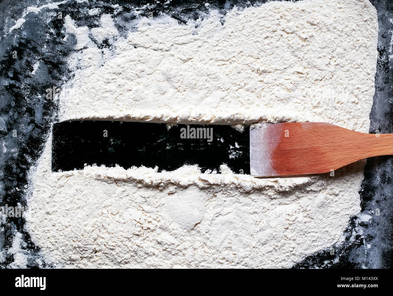 kitchen wooden spatula drew on a background of white crumbly flour a ...