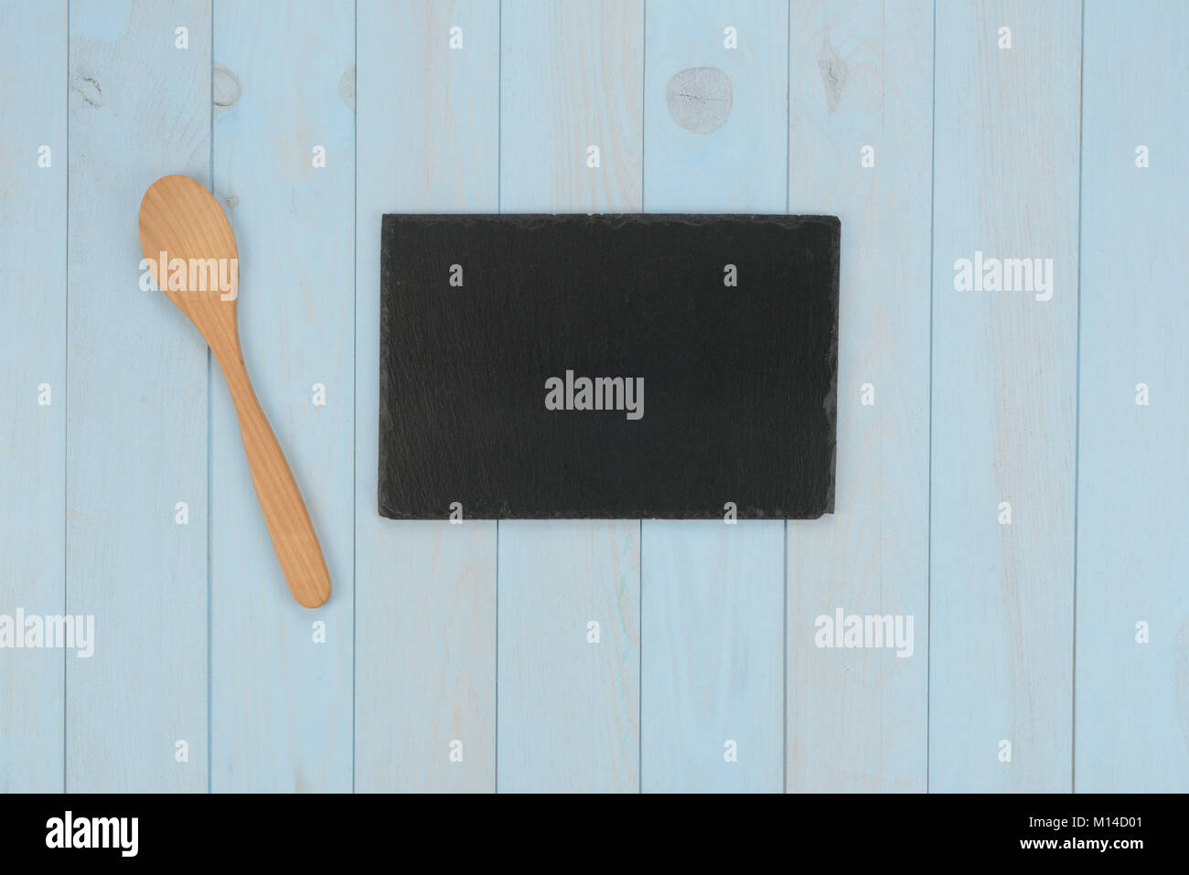 kitchen items wooden spoon and black stone plate on blue wooden