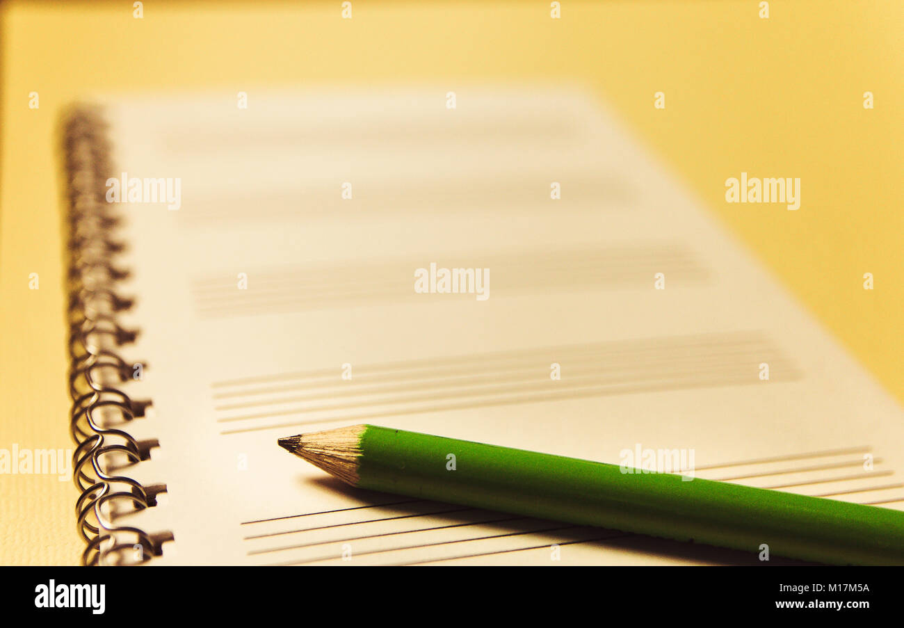 notebook and a green pencil on yellow background office theme stock