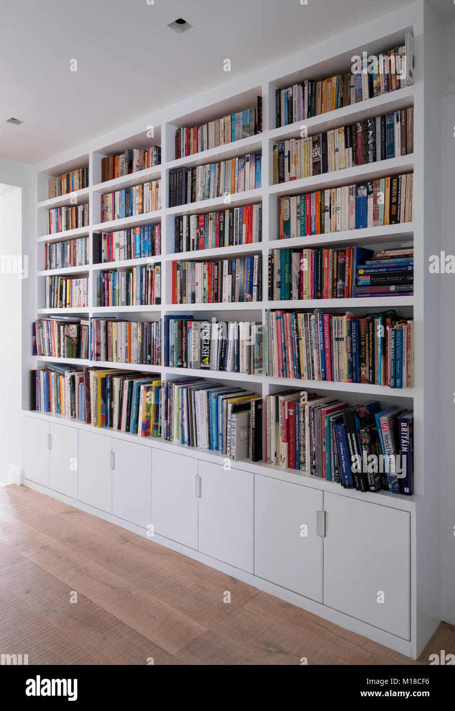white painted bookshelves full of books covering whole wall with cupboards under - Full Wall Bookshelves