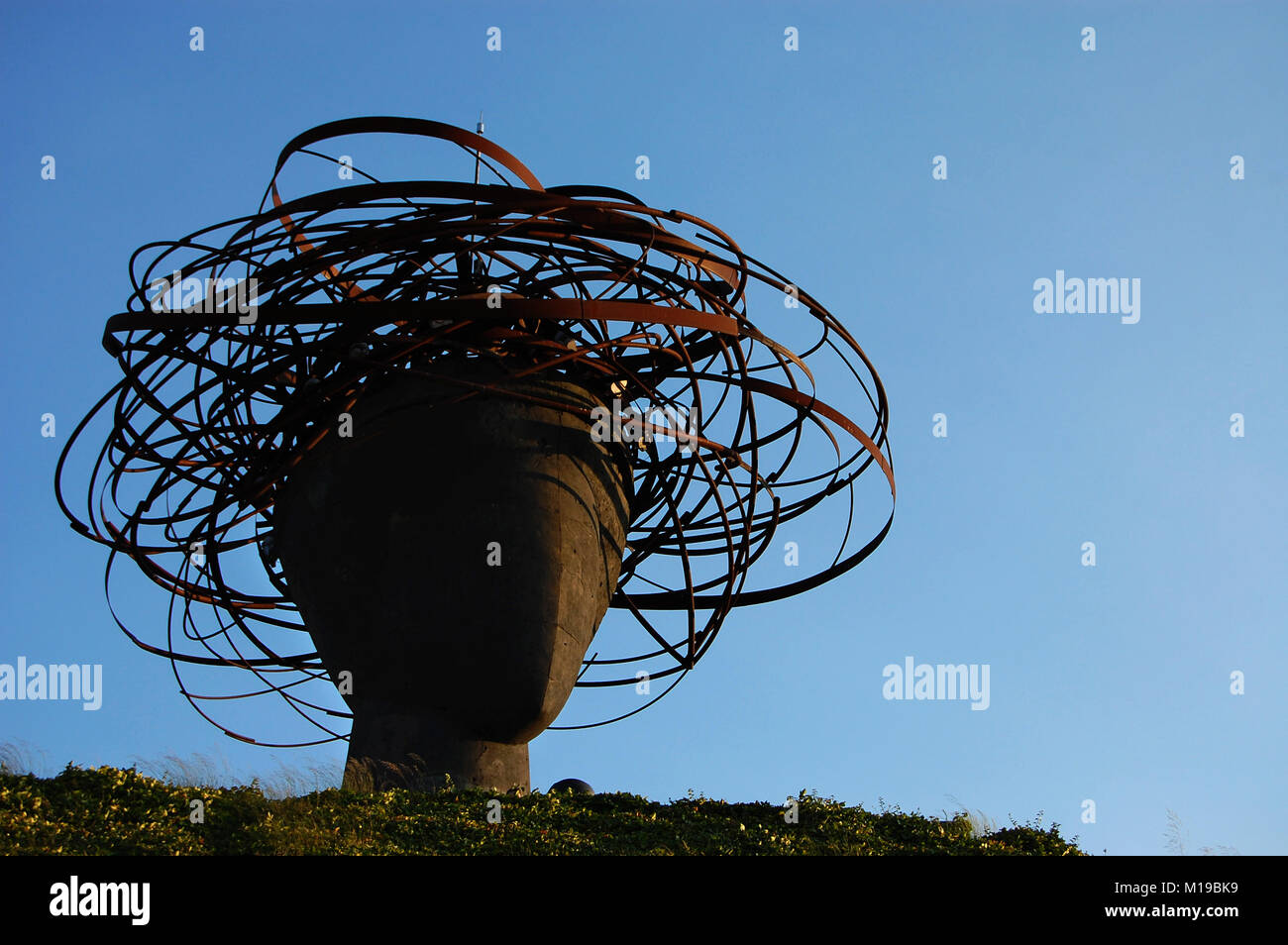 Iron head sculpture with headdress in a park with the sky in the ...