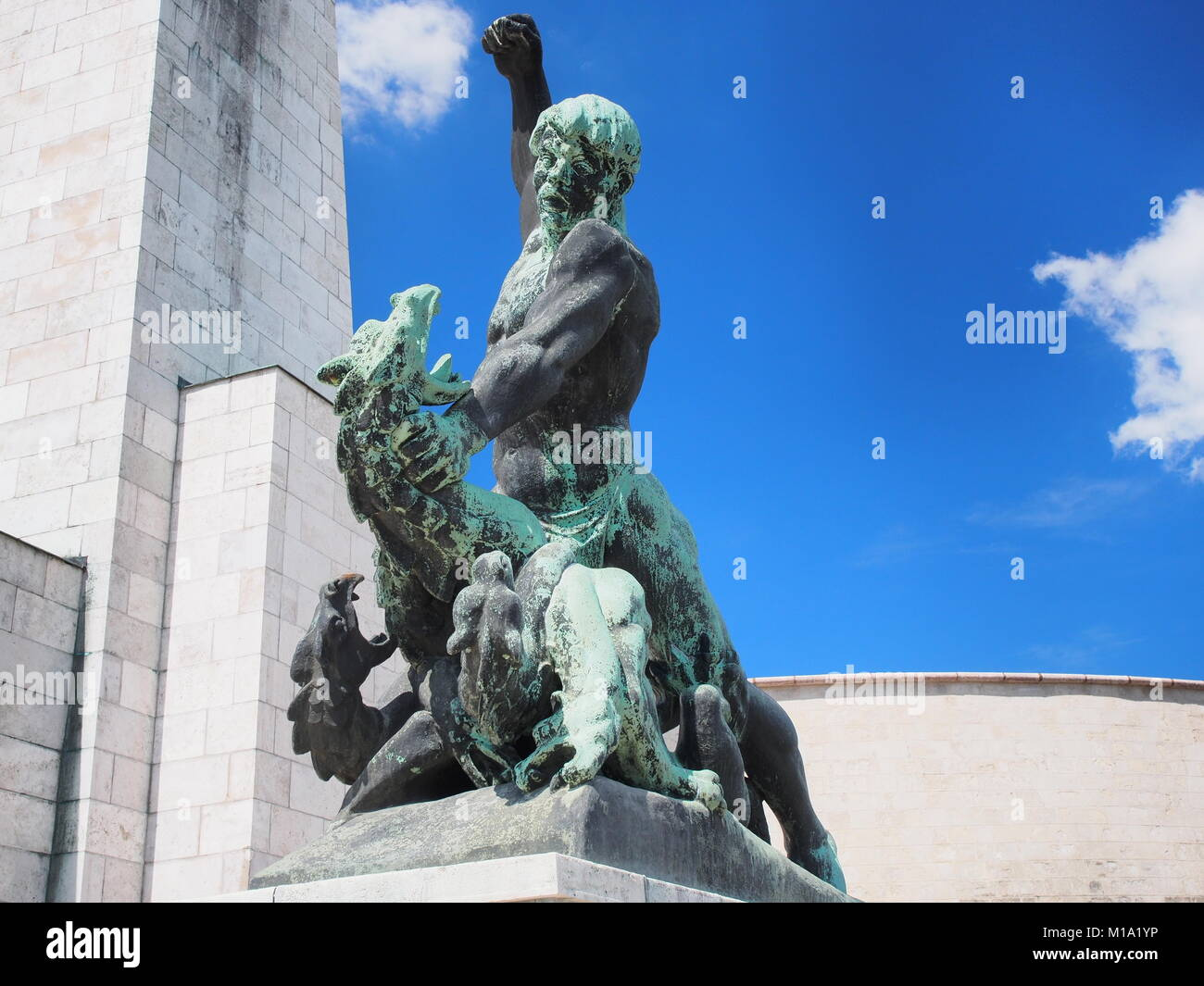 statue of a man fighting a mythical creature representing evil on