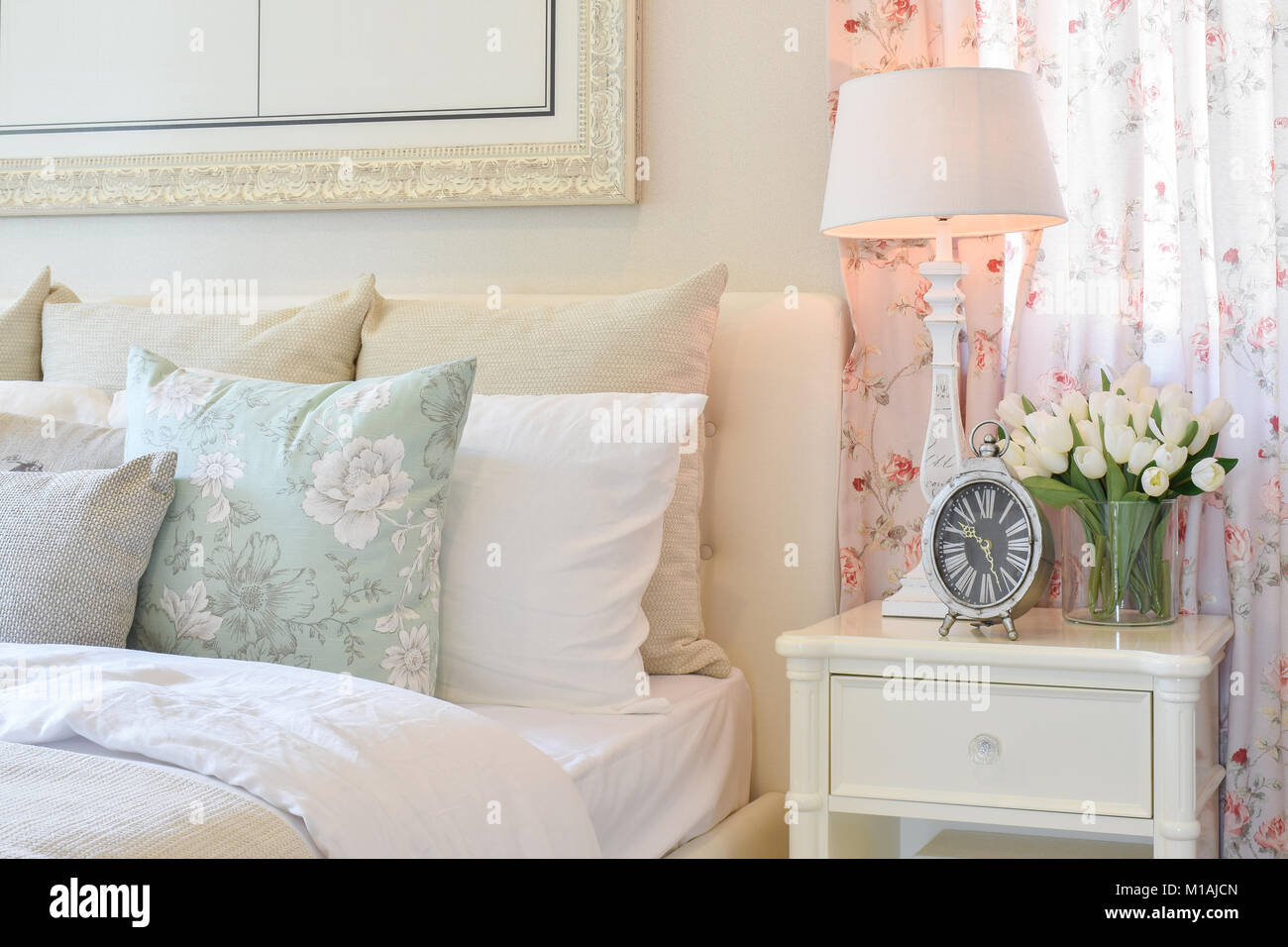 vintage bedroom interior with decorative table lamp, alarm clock and ...