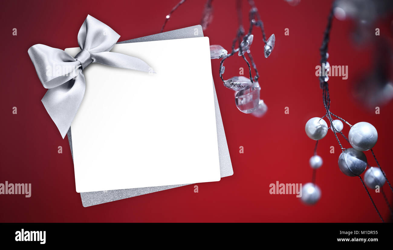 christmas greeting gift card with silver ribbon bow and mistletoe on
