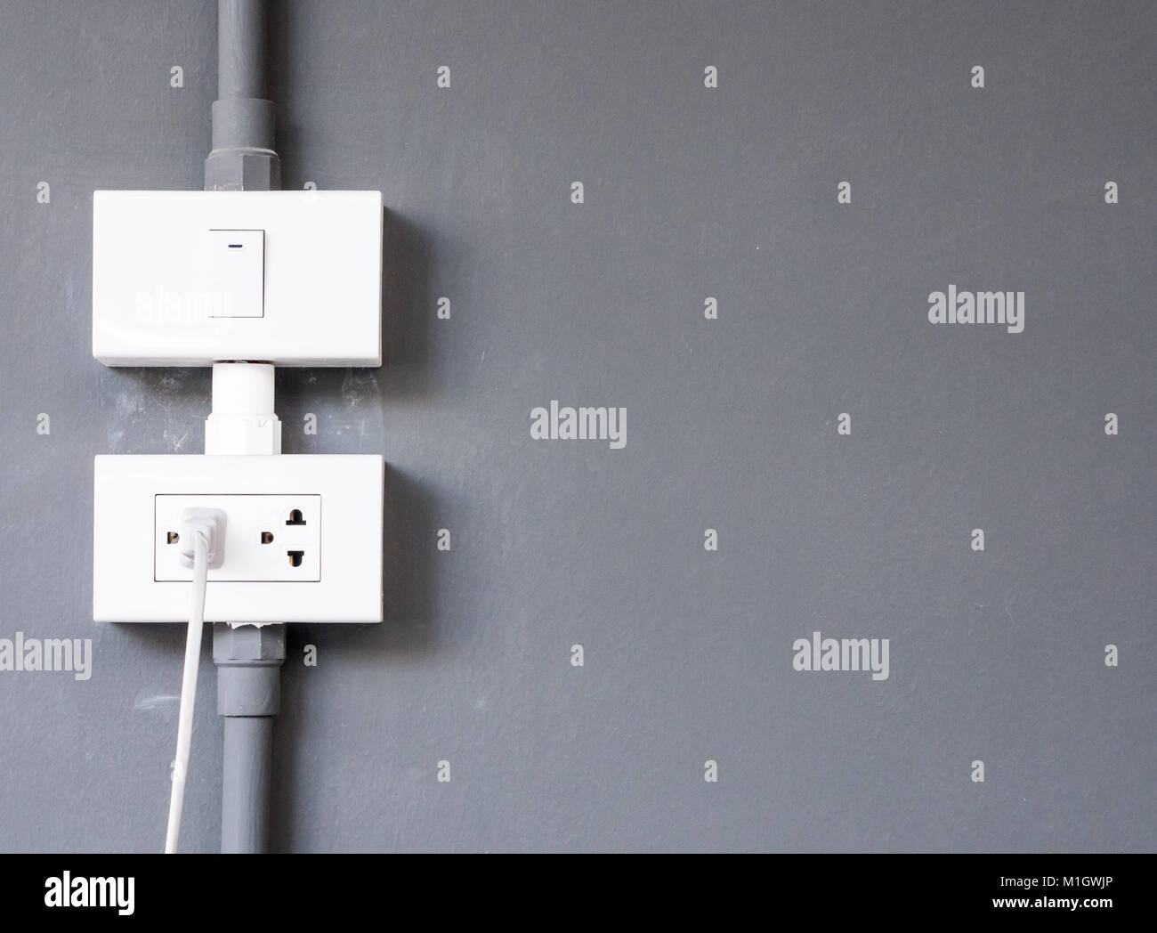 White electrical outlet with the wire and light bulb switch on the ...