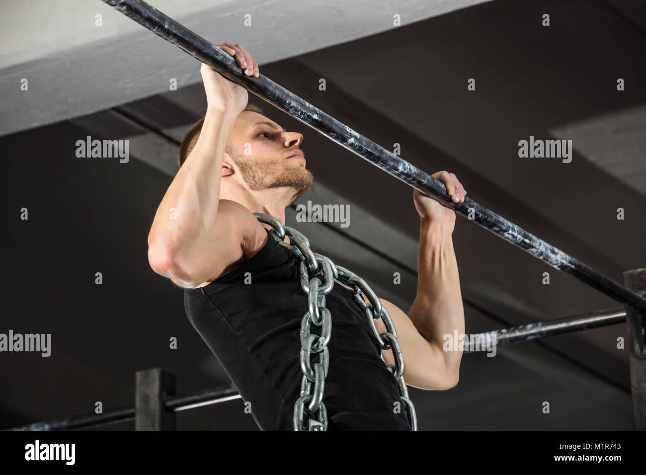 athlete man wearing a metal chain doing pull ups on horizontal bar