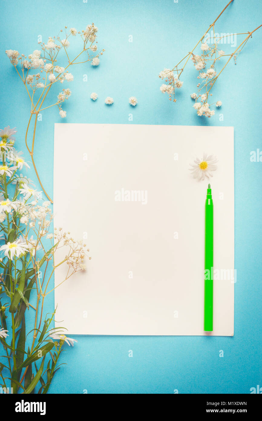 Pretty white flowers on blank paper with pen for greeting note pretty white flowers on blank paper with pen for greeting note list or drawing on blue background top view mightylinksfo