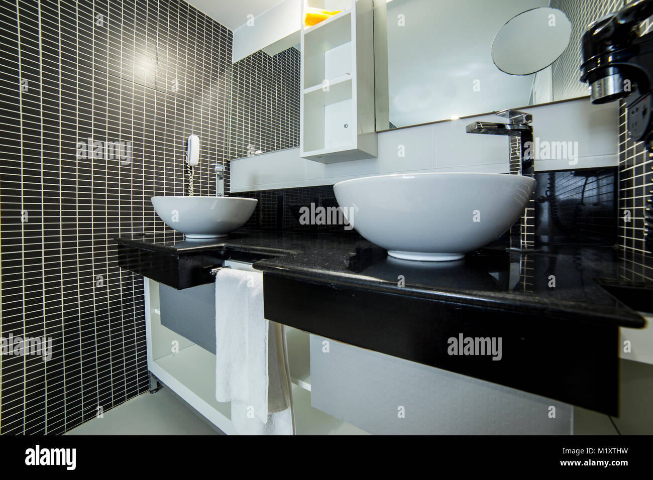 View of elegant bathroom with black tiles, wide angle lens image may ...