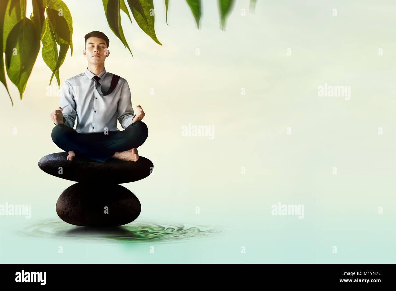 young businessman siting on zen rock with yoga meditation posture to