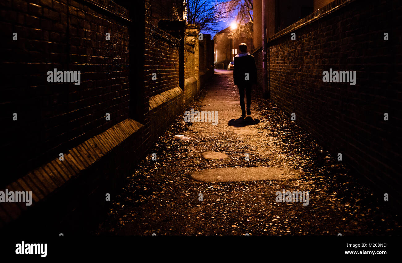 a young man walking home alone at night through a dark alleyway in