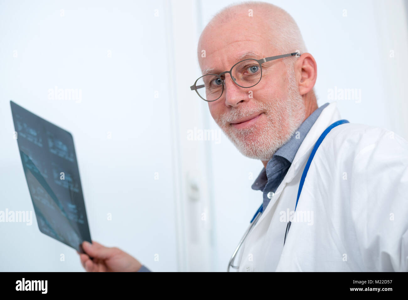 a mature doctor looking at an x-ray in an office stock photo