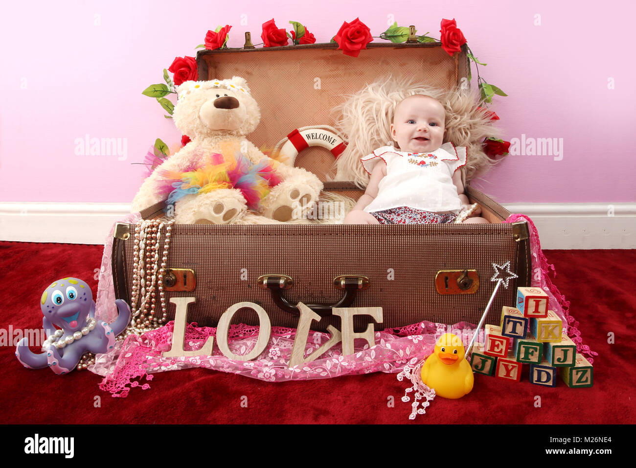 beautiful 3 month old baby girl happy playing in suitcase full of toys
