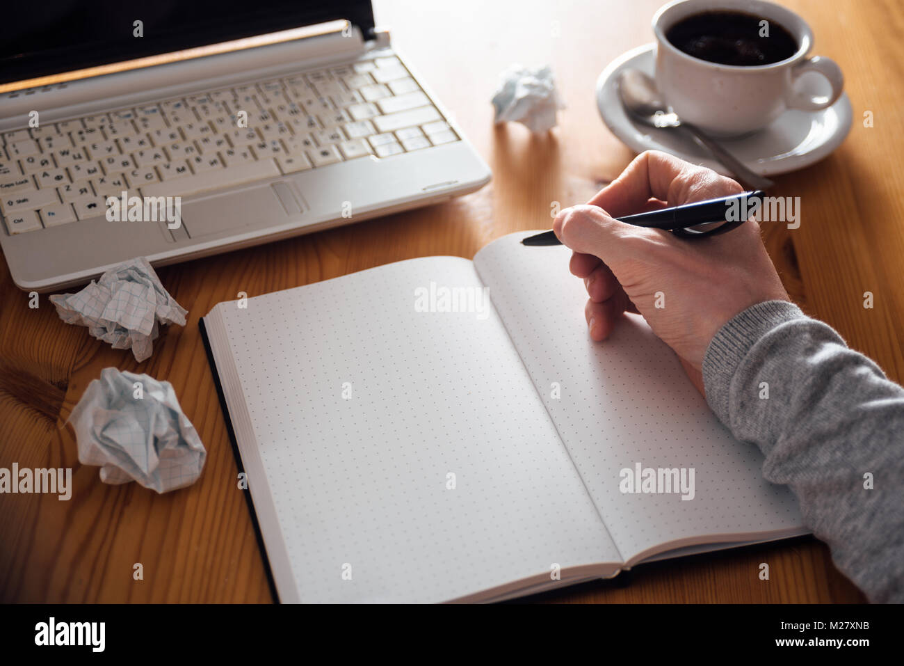 man hand writing in planner coffee laptop on background stock