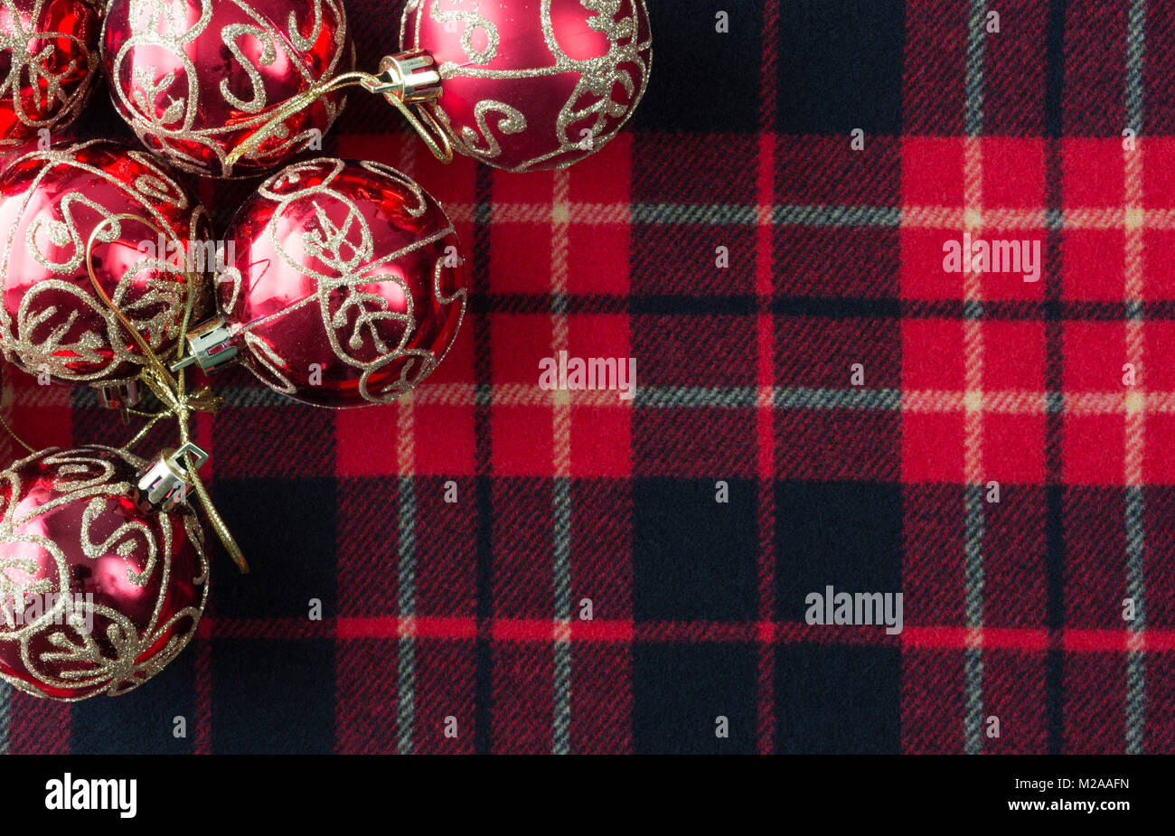 top view of several christmas ornaments atop a red black and white tartan cloth with room for a message