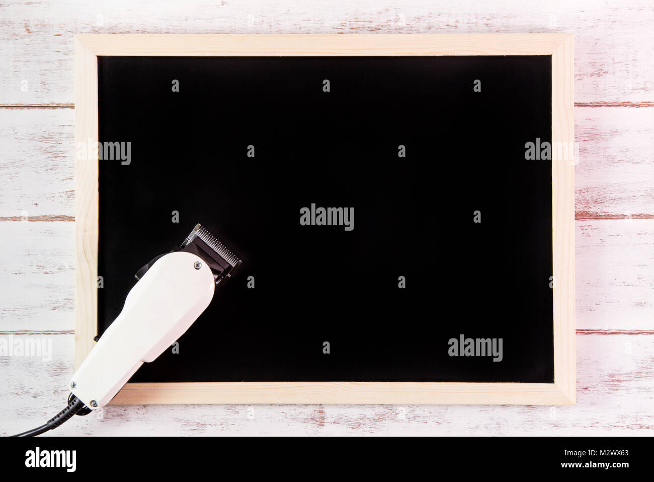 blank blackboard and clipper barber on wooden table template mock up