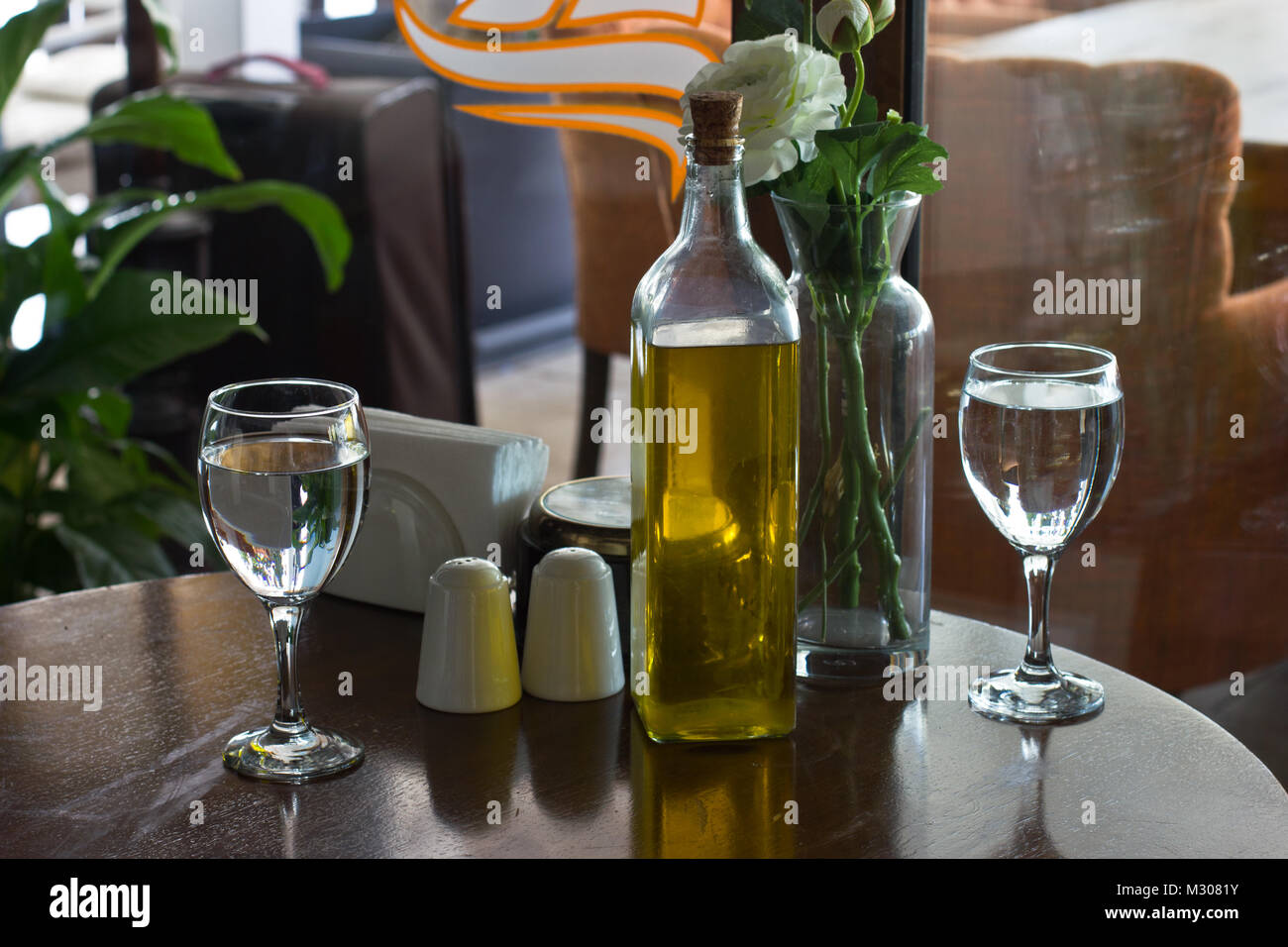 A bottle of olive oil on a table two glasses of water vase with a bottle of olive oil on a table two glasses of water vase with flowers the salt cellar reviewsmspy