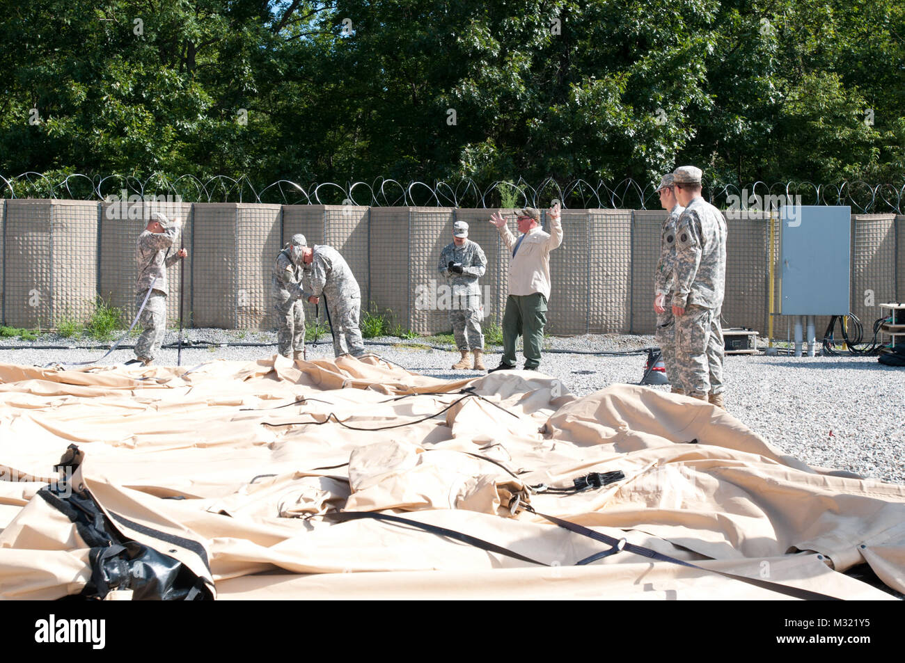 Soldiers of the 542nd Quartermaster Company unfold an air-supported tent to set up as & Soldiers of the 542nd Quartermaster Company unfold an air ...