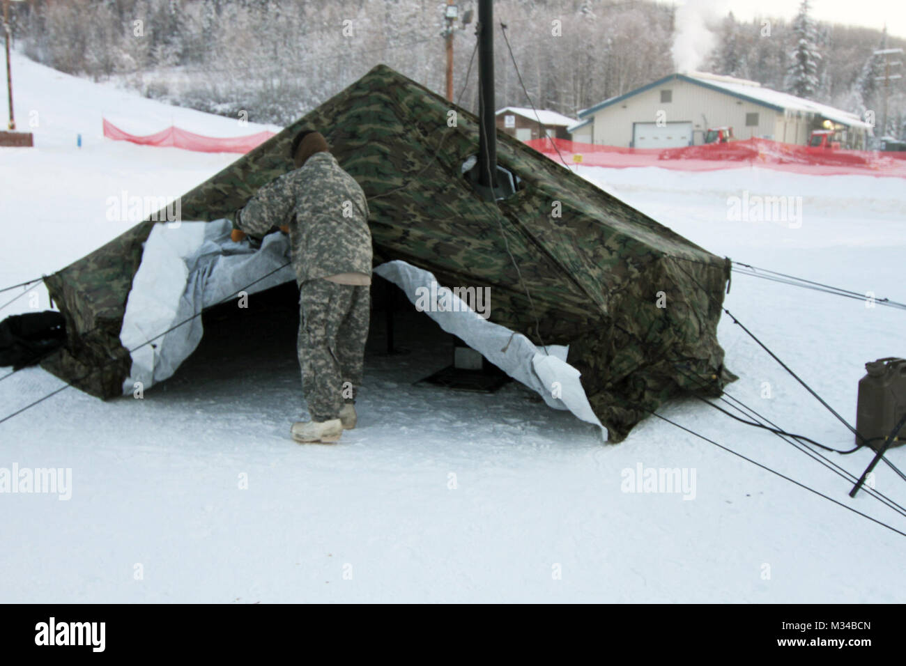 A Soldier from the Northern Warfare Training Center sets up an arctic tent as part of & A Soldier from the Northern Warfare Training Center sets up an ...