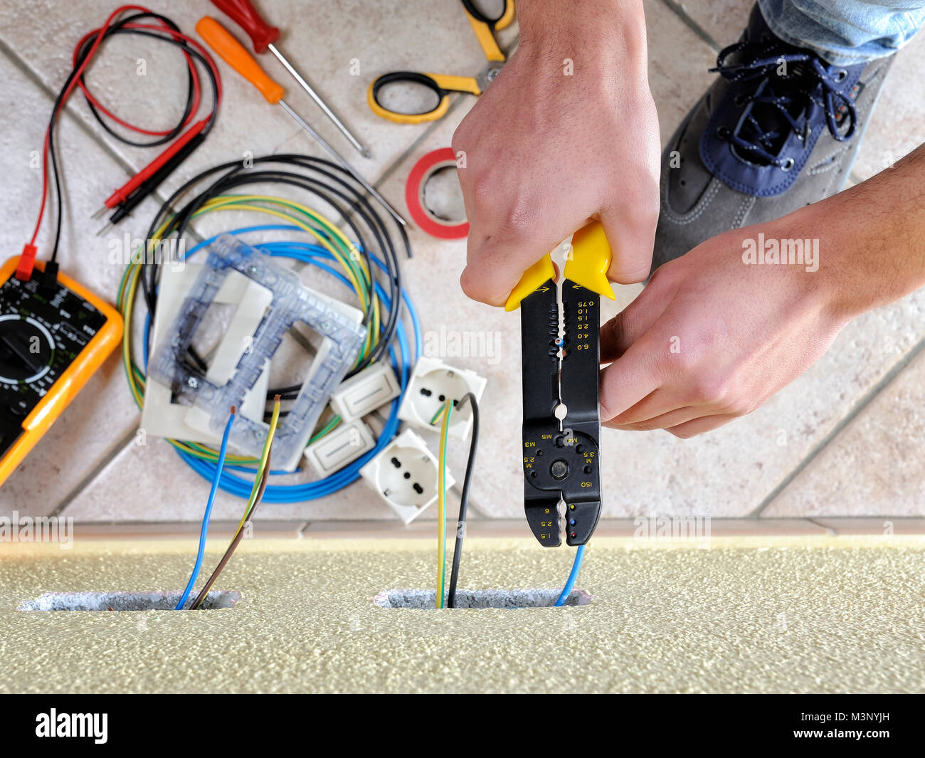 Electrician technician at work uses the wire stripper in a Stock ...