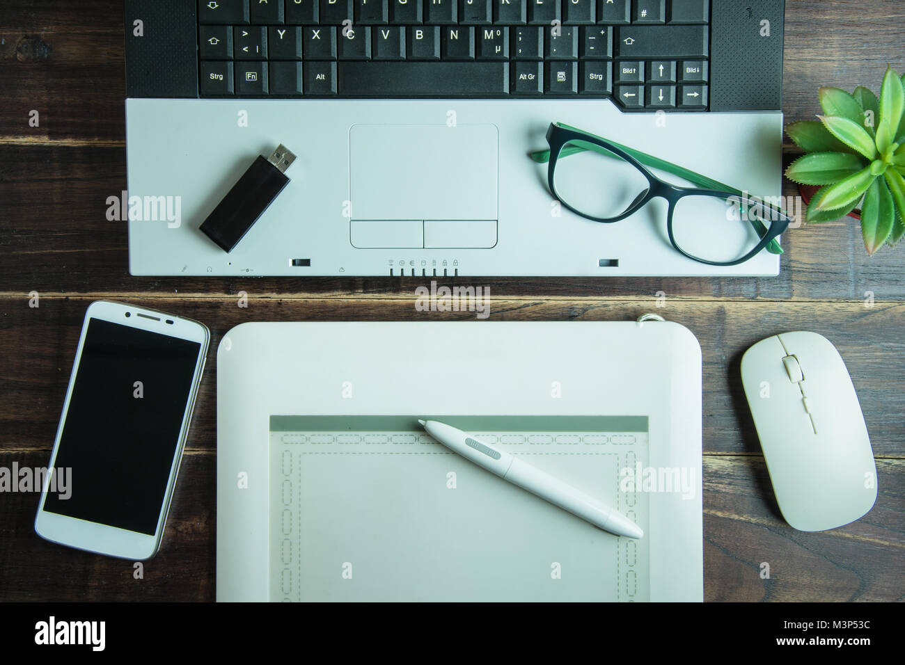 Top View Of Office Stuff Graphic Design With Pen Mouse Pad Laptop Wireless  Mouse And Smart Phone On Wooden Table.Concept Graphic Design Workplace