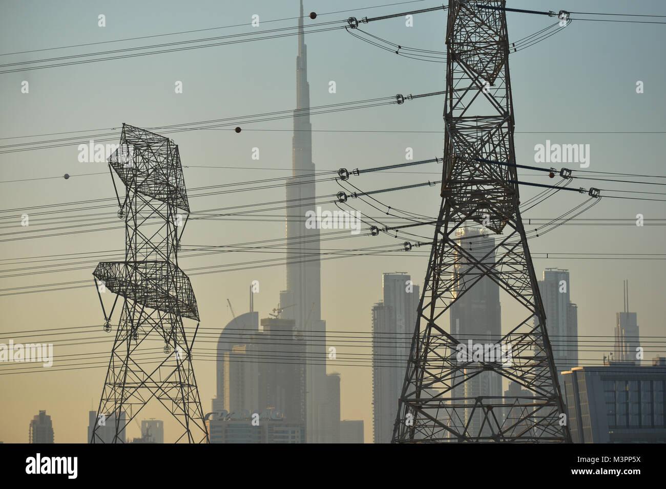 DUBAI, UAE - FEBRUARY 11, 2018. A view of Burg Khalifa and Dubaicenter seen  trough the electric wires network alongside of a motorway near Dubai.