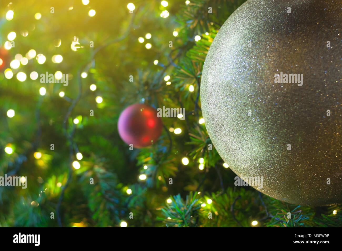 close up big yellow glitter ball christmas on tree with wire white light background