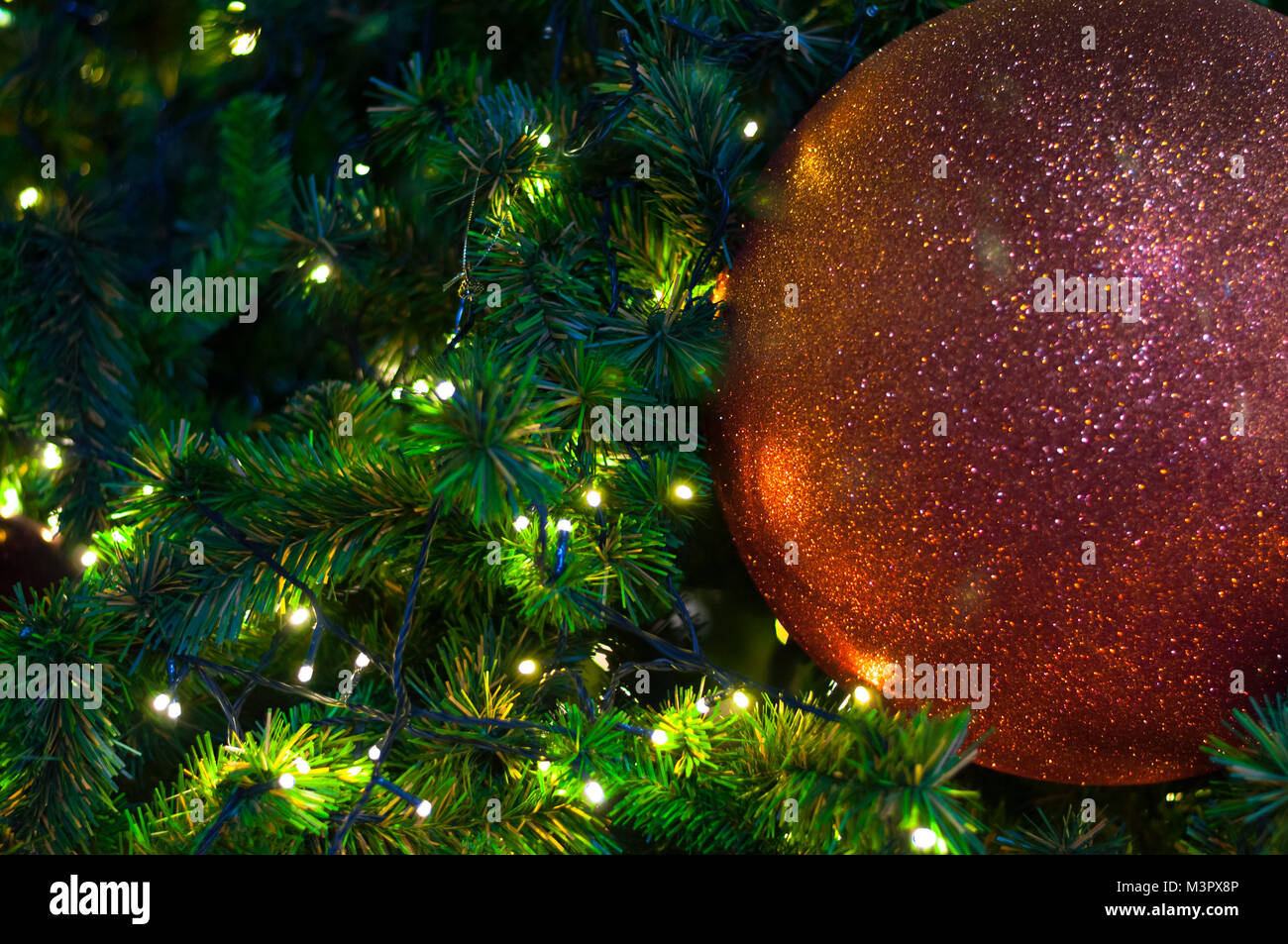 close up big red glitter ball christmas on tree with wire white light background