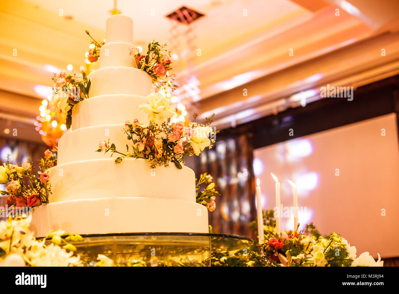Candlestick and wedding cake on the glass table at the stage in ...